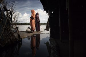 Bangladesh, Chalna, September 2010. Two women near their huts in the village of Chalna during floods. Their homes are increasingly threatened by rising water.This area in Bengala Bay is particularly affected by flooding. The cyclones, floods and monsoons hit the Bengal Bay annually causes the destruction of harvests and of entire villages because of increased rainfalls and sedimentation in river flow. The people who inhabit in this area are forced to migrate to Dahka slums with their children and live in dangerous and inhumane conditions.