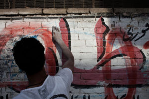 Member of the Ultras Ahlawy doing an illegal wall painting in Cairo's district Matareya