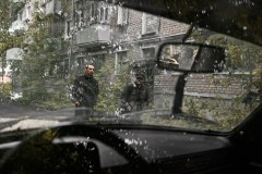 """Perm, Russia - May 2012.Passers trough the window of one the most exclusive soviet time cars """"Volga""""."""