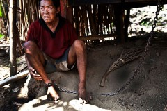 Bali, Indonesia, November 2011. Nengah, 56 years old, schizophrenic for 11 years, in chain for 5 years. His family doesn't release him otherwise he becomes aggressive.