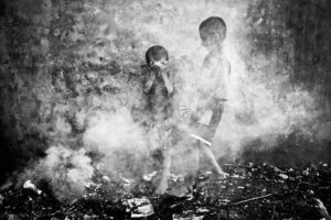 Chittagong, Bangladesh- June 2012. Two roaming boys of Chittagong Railway Station were playing in the smoke created from burnt straws during winter.