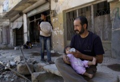 A man and his daughter outside his partially destroyed house in Azaz, on the outskirts of Aleppo. Syria, August 28, 2012<br>© Muhammed Muheisen / Associated Press.