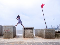 29070: A little girl jumps with a steel glass as red flag roars with wind , she stays in the small hut which is enclosed to the pavement.