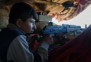 Kobane, Syria. 26 Decenber 2014: Armed  fighter of the Syrian Kurdish People's Protection Units (YPG) are seen on the defense line around Kobane the Syrian besieged border town of Ain al-Arab also named Kobanê.