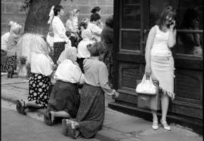Lviv, Ukraine - June 2006 Girl with mobile ocassionally encounters a street prayer