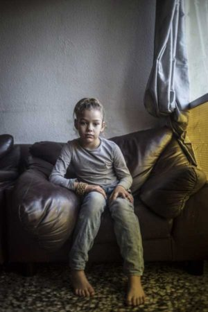 SAN ROQUE, SPAIN – December 2014. 7- year old Carmen in her families living room. Carmen is one of 7 children, living with their parents in a tiny quat.