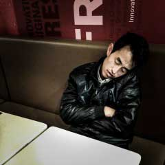 Beijing, April 2013. A drunk man sleeps over in a fast food nearby Guijie.
