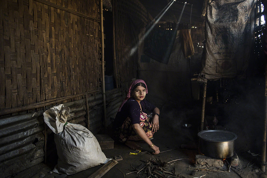 © Lynsey Addario. Aisha, 18, cooks in her family home in Say Tha Mar Gyi Camp (Myanmar). Aisha is married, but her husband left her within the last year to return to his family.