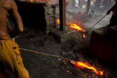 Kolkata,India-July 2015. semi liquid hot iron is getting cleared from the floor