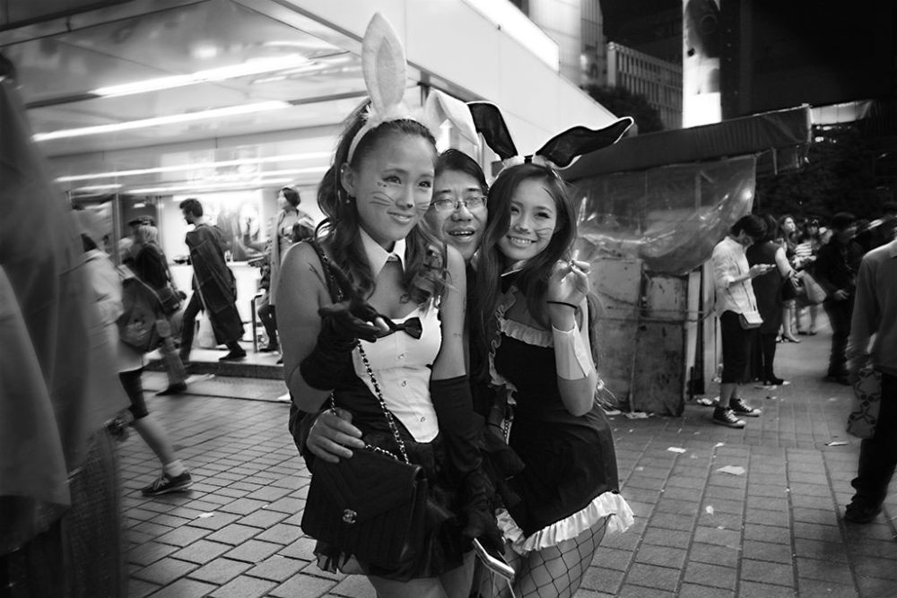 TOKYO, JAPAN - October 2015. 'Salaryman' poses with Playboy bunnies.