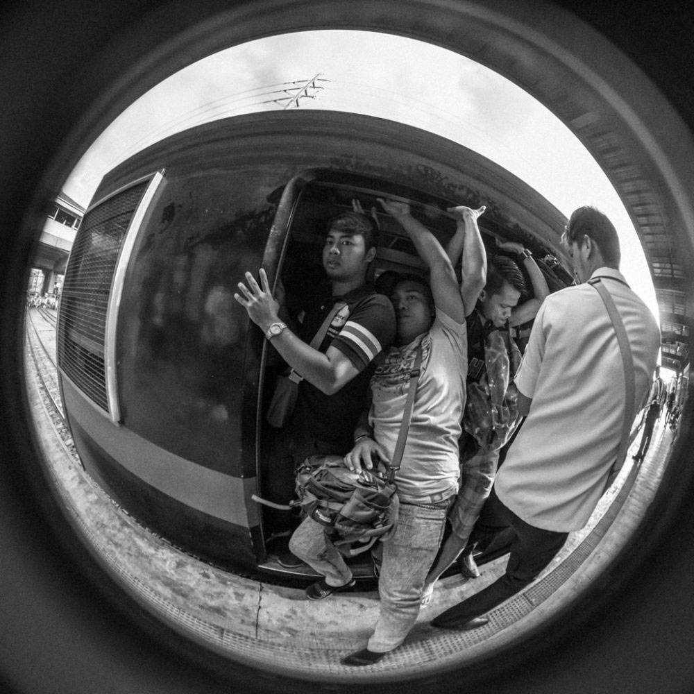 Men struggle to fit inside a train carriage on one of the older and more inexpensive railways in Manila, the Philippines.