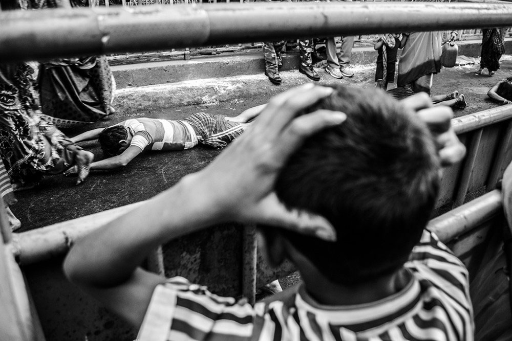 Howrah, India, February 2016, A child is struck with awe and fear as he sees his father struggle down the road on his chests