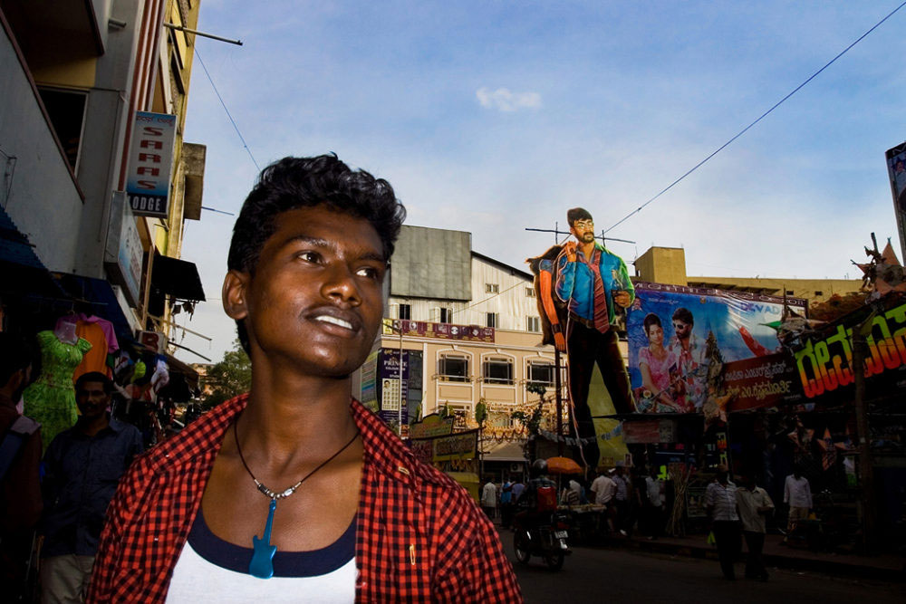 Bangalore, India - April 2014 - Another migrated man juxtapose with a huge poster of a hero of indian Movie