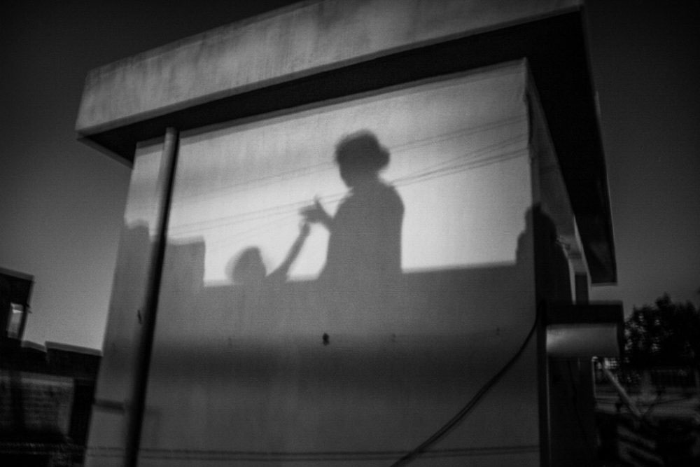 8. KOLKATA, INDIA - June 2016. Shadow of Shreyasee and her daughter while she was playing with her child on the rooftop. Just like my mother Shreyasee has to serve the role of both mother and father for her child