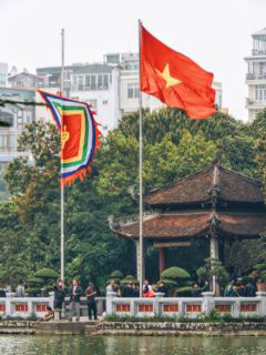 HANOI, VIETNAM - March 2016. The five-coloured flag is symbolic to Vietnam and demarcates a place of worship. This was shot at the famous Hoàn Kiêm Lake in central Hanoi which houses the Temple of the Jade Mountain, a popular spot for tourists.