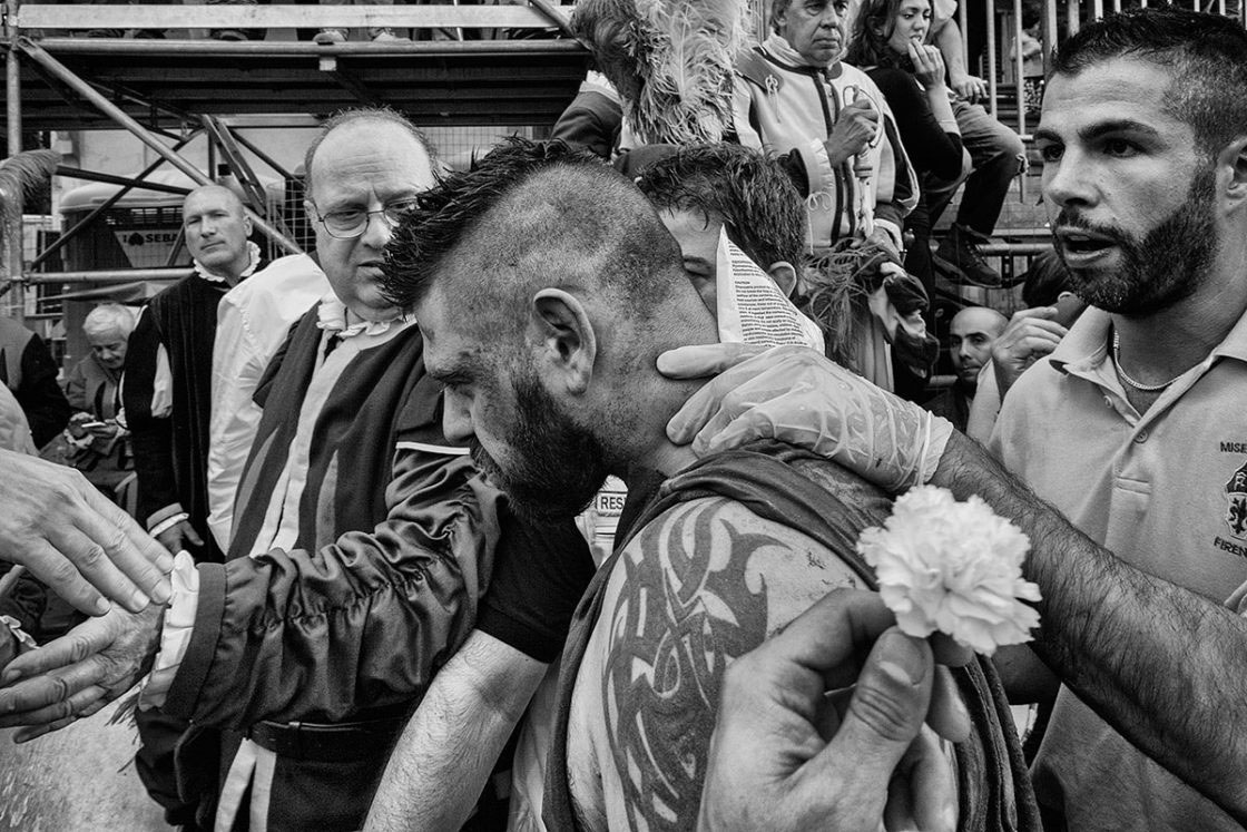 """Florence, Italy - June 2016; a Calciante (player of Calcio) of the Verdi (""""Greens"""") di San Giovanni team is escorted by a paramedic out of the field after having received a violent jab during a match of Calcio Fiorentino."""