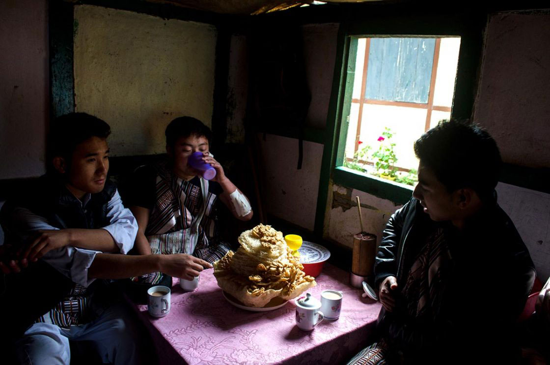 "Sikkim, India- December 2015. Group of traditionally dressed ""Lepcha"" performer is having home made sweet snacks ""Zeroo"", ""Kabje"", ""Paumulangcho"" and home made wine, ""Chi"" at a Lepcha house of Sahri Kopibari Village, just before ""Namsung"" special performance. Namsung is a five day's festival celebrated by Lepcha community to offering thanks to God for good harvest, as well as this is the festival to welcome Tibetan upcoming year."