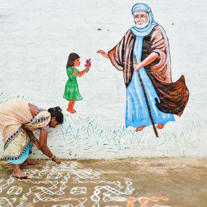 India - Apri 2017. A woman painting colorful motifs near temple