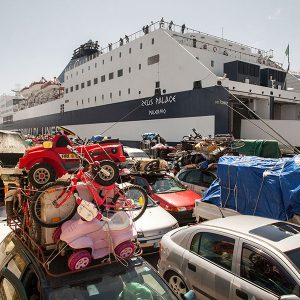 PALERMO, ITALY - May 2014. A crowd of cars belonging to Tunisian immigrants wait at the port to board on the ferry that connects Palermo and Tunis (Tunisia). Some Tunisian immigrants have built a business between Europe and Africa buying second hand products in Italy to sell them in Tunisia. All the goods are piled on the cars' roof and brought to Tunisia on a passenger ferry. In the background the ferry is landing at Palermo port.