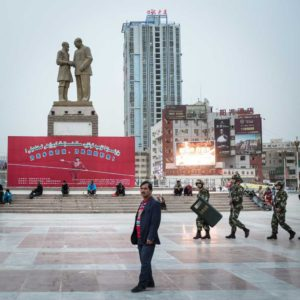 Hotan, Xinjiang, China, 26/03/2015 - A Uighur man standing on Hotan main square as members of the People's Liberation Army are walking behind him. The statue on the left shows Mao Zedong shaking hands with an old Uighur named Kurban Tulum who travelled miles on his donkey to congratulate Mao Zedong. © Raphaël Fournier / Divergence