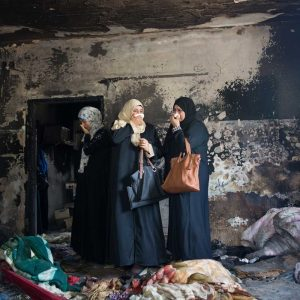 Palestinian women dismayed at the sight of .the house of the Dawabsheh family, Duma village, south of Nablus, 3 August 2015