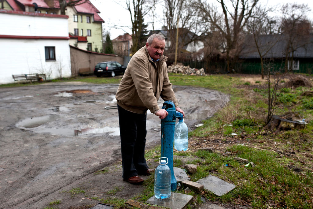 Zamosc, Poland - April, 2015. A local man collects water in Zamosc.
