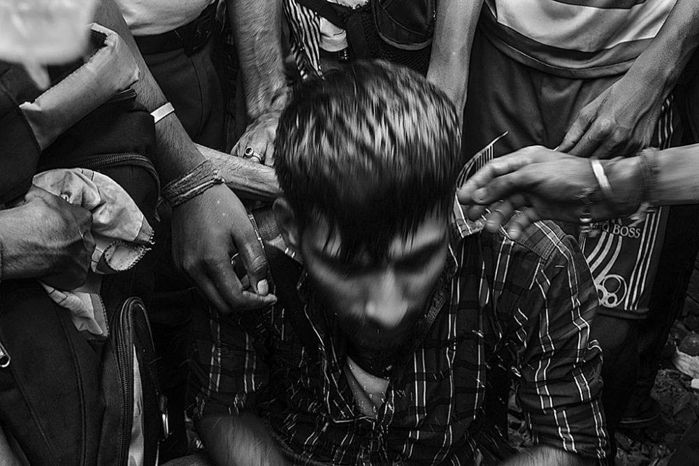 Birati, Kolkata, India - 19th August 2015. Few people among the mass sprinkled water on a young protester's face who sat down in between the running mass, as no such proper step lodged against the accused lady who threw the grandfather along with his grandson.
