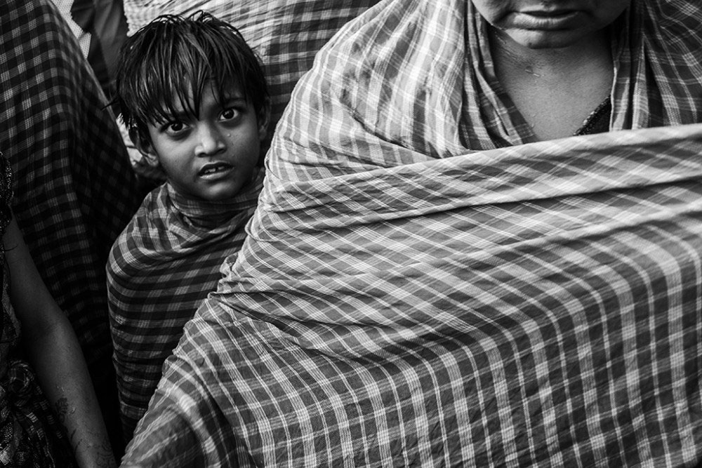 Howrah,India, February 2016, A boy looks, just before taking a dip in the Ganges, surrounded by his family