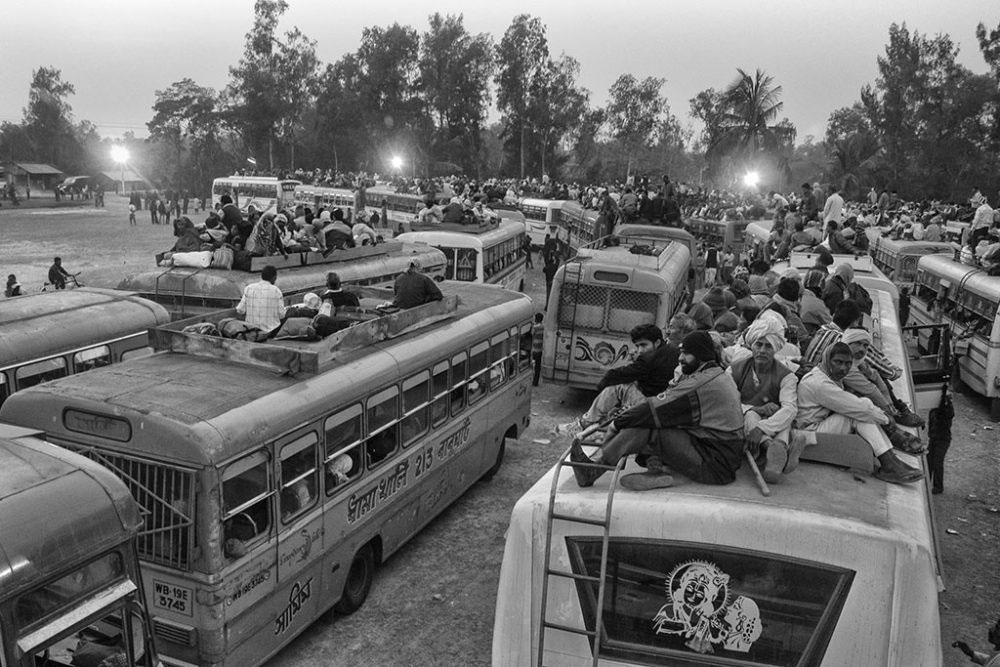 Gangasagar, West Bengal, 14th January'14 : People who can't manage a sit inside, forced to get on to the roof of the bus.