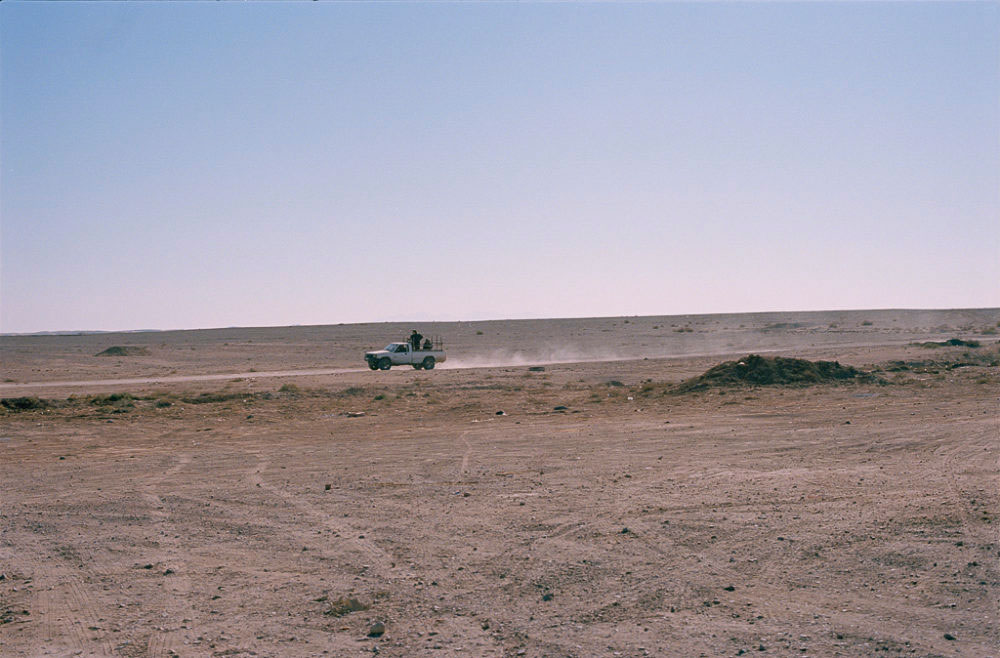 Vehicle with men on the back passing by in Maranjab desert, Kashan, Iran, November 2015