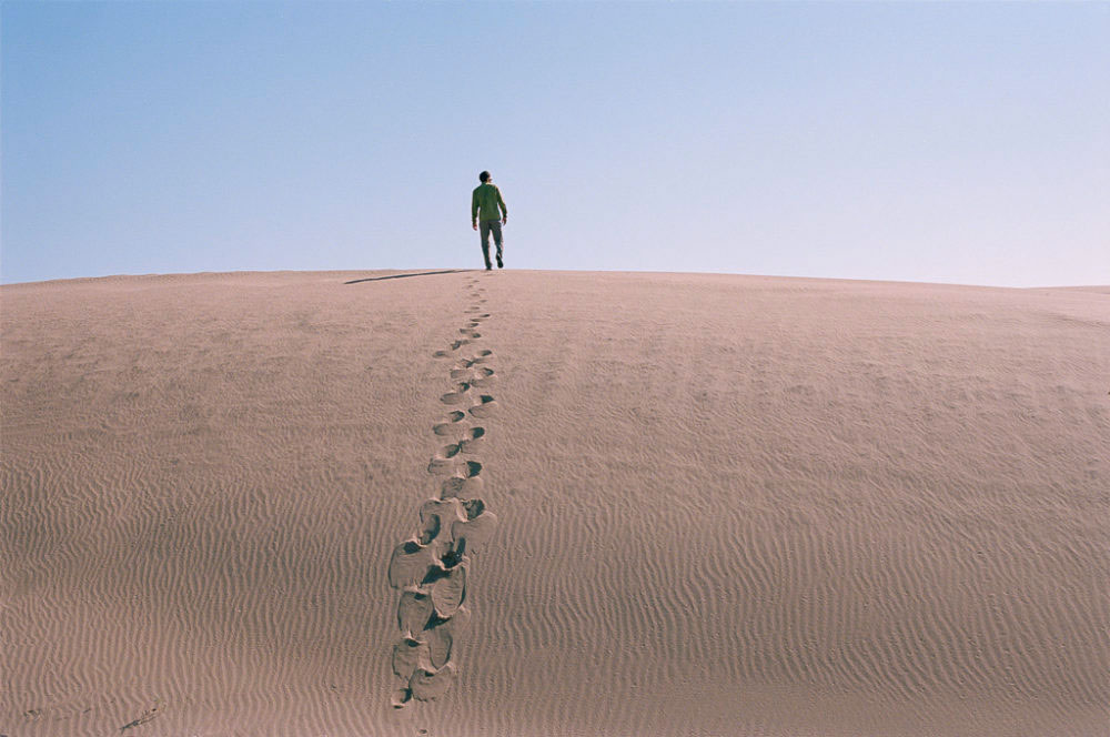 Man in a sand dune in Maranjab desert, Kashan, Iran, November 2015