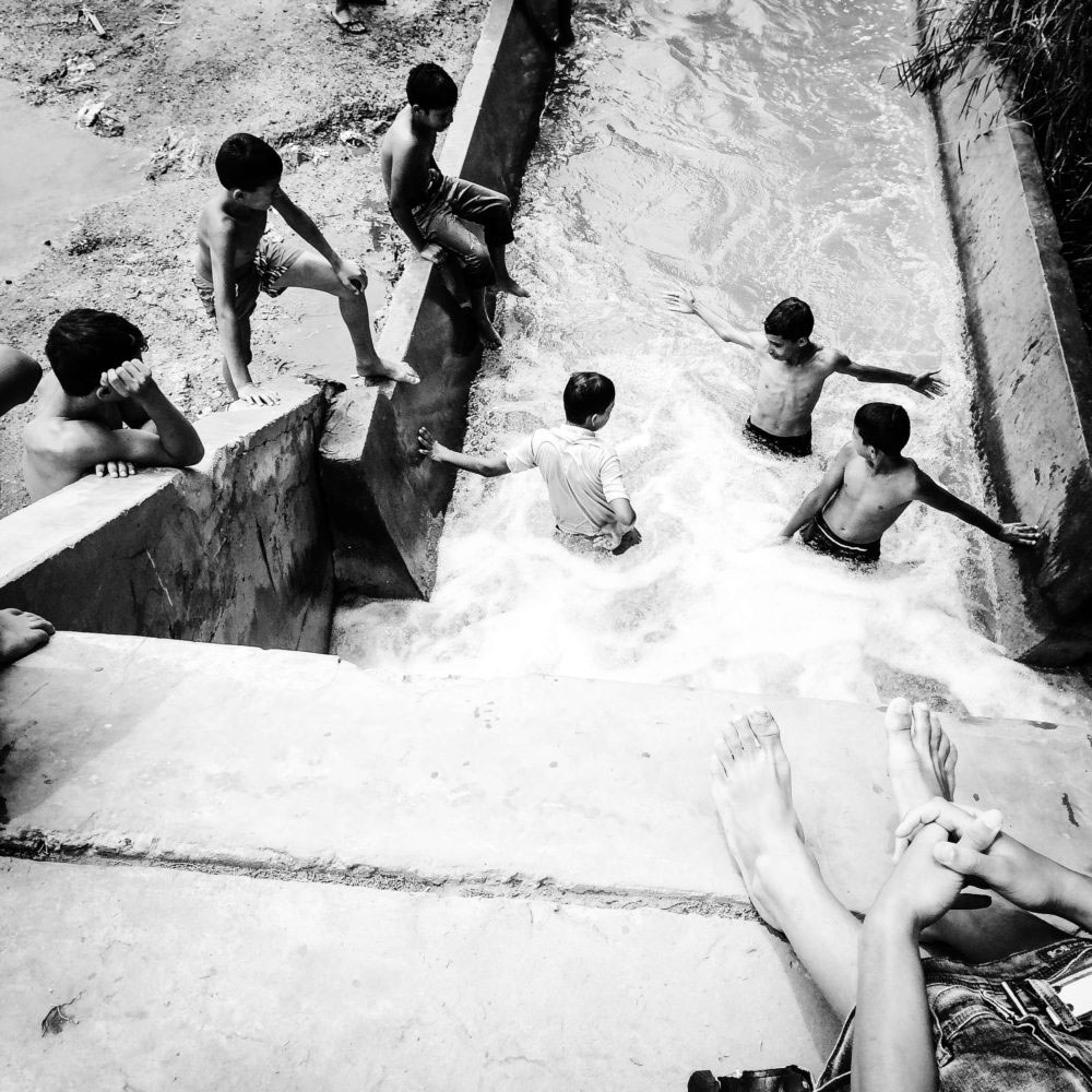 Young boys taking a swim in large irrigation channels,Relizane,June,27th,2016.