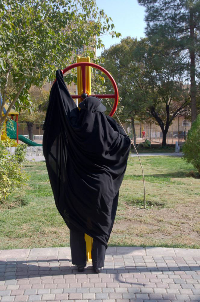 Tehran, Iran - November 2016. A woman is doing exercises wearing a long black chador.