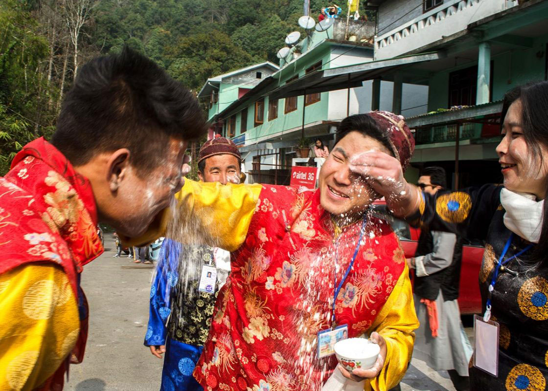 "Sikkim, India- December 2015. Group of traditionally dressed ""Bhutia"" performer is celebrating ""Lawsung"" by throw paddy flour to each other in front of Rumtek Monastery. Lawsung is a five day's festival to offering thanks to God for good harvest, as well as this is the festival to welcome Tibetan upcoming year."
