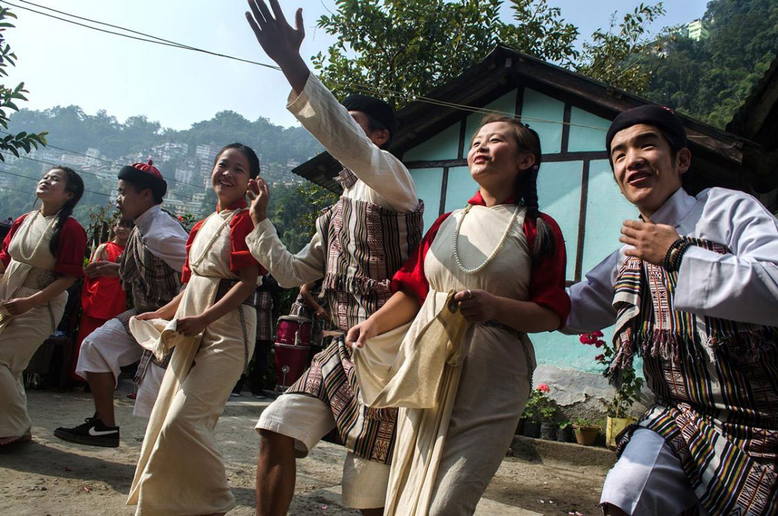 "Sikkim, India- December 2015. Group of ""Lepcha"" performer dressed traditionally dancing with traditional song at Sehri Kopibari. Thanks giving festival ""Namsung"" is celebrated mostly with family members and friends, a performing group goes house to house to show their charisma on traditional song and dance. House lord gives them Tea, sweet snacks ""Zeroo"", ""Kabje"", ""Paumulangcho"" and some gifts mainly money."