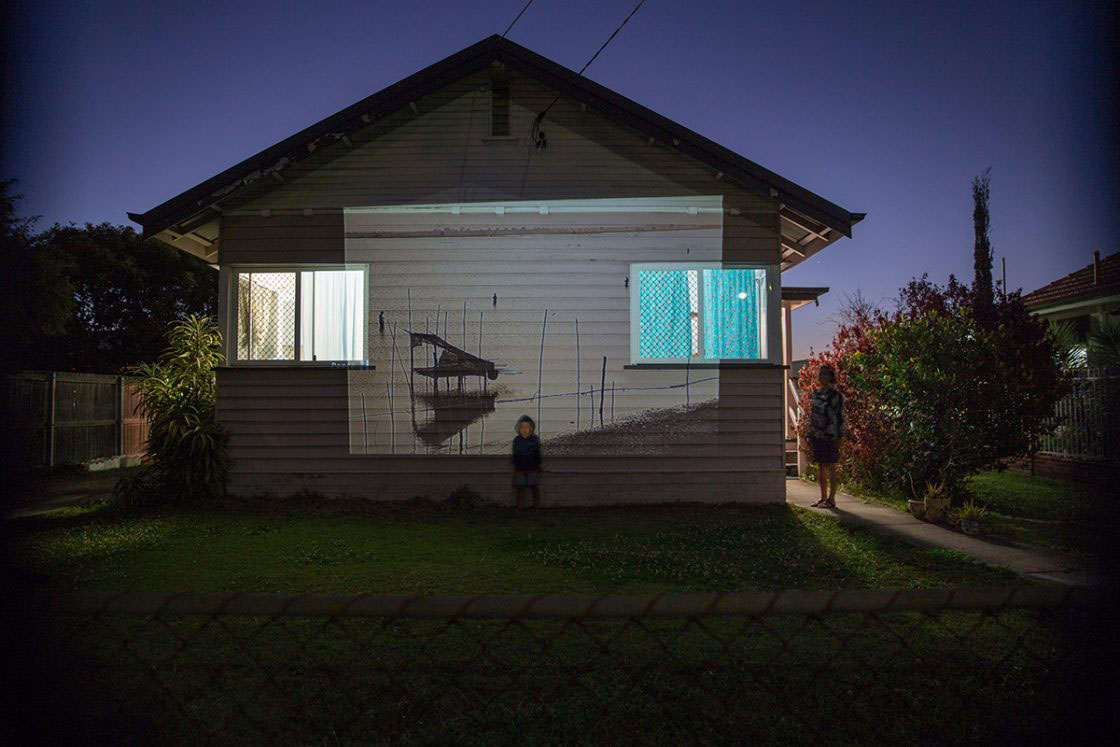 A projection of fishing families in Myanmar. This image has been projected onto the side of a house where a woman and her nephew stand outside their home in Brisbane, Australia. Fish is a staple of the Burmese diet and many who have resettled have told stories of getting caught fishing illegally fishing in newly settled areas as it can be difficult to navigate the local rules and regulations. BRISBANE, AUSTRALIA - September 2015.