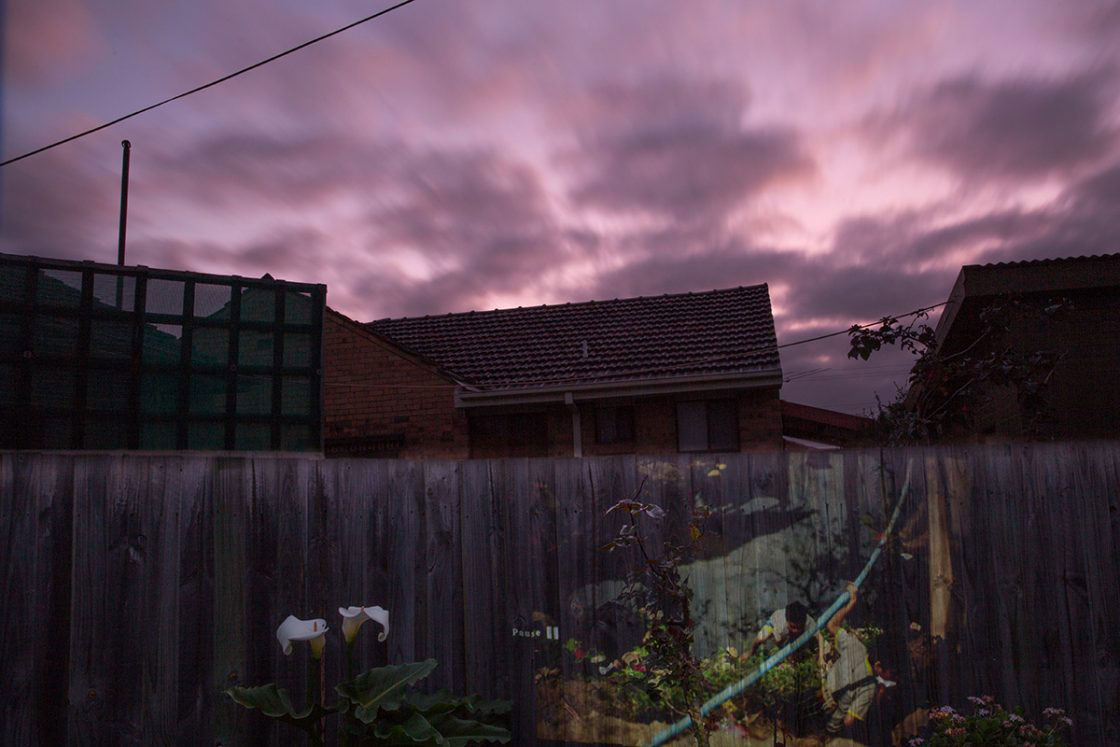 A projection of children crossing zones in Mae La refugee camp on the fence line between two neighbourhood homes in suburban Victoria, Australia. VICTORIA, AUSTRALIA - August 2015.
