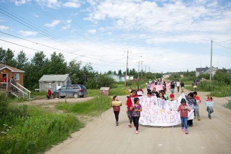 Children lead an Awareness Walk against drug dealing and bootlegging on Fourth Street in Fort Albany First Nation, Ontario, Canada. July 21, 2016. In October 2016 a thirteen-year-old boy, at the front of the line in the Awareness Walk, took his own life.