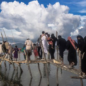 Teknaf, Bangladesh - September 2017. Rohingya refugees crossing temporary bridge made with bamboo near Shah Parir Dwip, Teknaf.