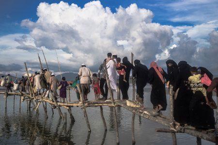 Teknaf, Bangladesh - September 2017. Rohingya refugees crossing temporary bridge made with bamboo near Shah Parir Dwip, Teknaf.